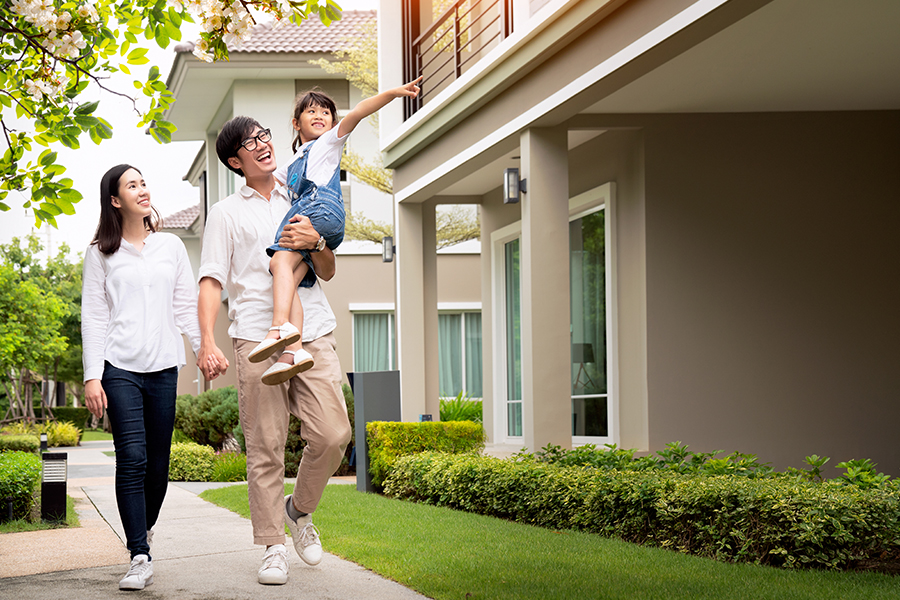 Personal Insurance - Family Walking Down a Tree Lined Sidewalk Before Entering New Home on a Sunny Day